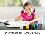 little girl is painting picture | Shutterstock . vector #698017699