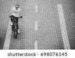 BRATISLAVA, SLOVAKIA - August 12, 2017: A cycling girl with a helmet on the bike lane in the park - stock photo