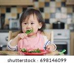 baby girl eating  vegetable at... | Shutterstock . vector #698146099