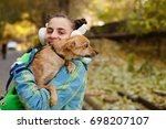 the girl is holding a small dog ... | Shutterstock . vector #698207107