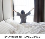 woman stretching in bed after... | Shutterstock . vector #698225419