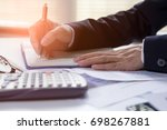 Small photo of Businessman writing on notebook on wooden table, People are recording accounting data calculated from a calculator.Concept finance planing and analyzes management.