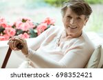 elder lady sitting on the couch ... | Shutterstock . vector #698352421