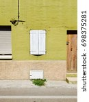 Small photo of Wooden white window of a green house - Building façade (Pesaro, Italy)