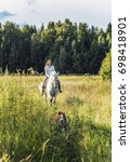 Young Woman Riding A Horse Wit...