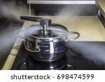pressure cooker releasing hot... | Shutterstock . vector #698474599