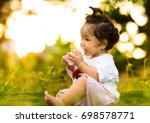 baby drinking water in green... | Shutterstock . vector #698578771
