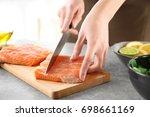 woman cutting fresh salmon...   Shutterstock . vector #698661169