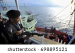 Small photo of MALAYSIA, 18 AUGUST 2017 - A maritime armed member who monitors movements from the deck when other members are investigating foreign fishing boats in the ocean at Terengganu 460km from Kuala Lumpur.