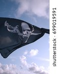 Small photo of Pirate flag - skull and crossbones, flying in the wind against a blue sky.