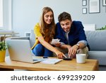 happy young couple paying bills ... | Shutterstock . vector #699239209
