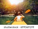purposeful woman paddling the... | Shutterstock . vector #699369199