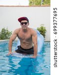 Small photo of Young strong man on an air bed in the pool.