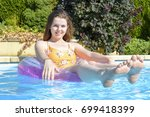 Smiling, teenage girl floating in an inflatable ring in an outdoor swimming pool - stock photo