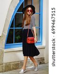 Small photo of Outdoor portrait of young beautiful girl with long hair walking in street. Model wearing stylish red sunglasses, black hat, striped blouse, dark blue skirt, slippers shoes, has small red bag