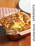 Small photo of Baked polenta with eggs, sausage and fontina in a red, ceramic baking bowl with a red and white stripped napkin on a wood serving board