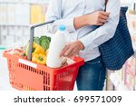 woman doing grocery shopping at ... | Shutterstock . vector #699571009