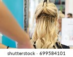 Small photo of Hairdresser applying blonde tress keratin or ceratine on clients blond hair in beauty salon. Hair extension.