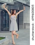 Small photo of Yeah! Young happy smiling woman triumphing with raised hands against entrance to the building