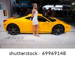 DETROIT - JANUARY 13: A model poses with a Ferrari 458 Italia at the 2011 North American International Auto Show Industry Preview on January 13, 2011 in Detroit, Michigan. - stock photo