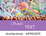 Decorative painted easter eggs in basket on purple background with copy space.  Macro with extremely shallow dof. - stock photo
