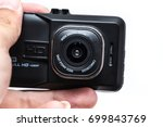 Small photo of closeup digital camera action cam or dash cam show font lens in hand on white background