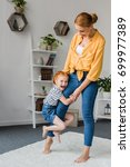 Small photo of mother and adorable daughter playing at home