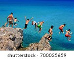 boys diving from the rocks at... | Shutterstock . vector #700025659