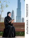 Small photo of Smiling arab woman in abaya holding tablet and looking in the camera.