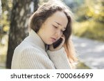 unhappy girl talking on the... | Shutterstock . vector #700066699