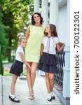 mother with two daughters is... | Shutterstock . vector #700122301
