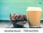 Small photo of Take away coffe and chocolate muffin on wooden background with copy space for text or advert