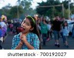 girl watching camera eating a... | Shutterstock . vector #700192027