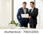 two smiling businessmen talking ... | Shutterstock . vector #700212001