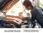 car mechanic in grey uniform... | Shutterstock . vector #700235041