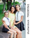 mother with two daughters is... | Shutterstock . vector #700285561