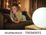 attractive girl lying on sofa... | Shutterstock . vector #700360051