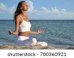 beautiful woman doing yoga at... | Shutterstock . vector #700360921