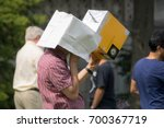 Small photo of Boston, MA, USA - August 21 2017: A man using a cardboard box with a pinhole to observe a partial solar eclipse.