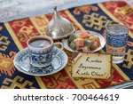 Small photo of Happy eid al adna text in turkish on greeting card with turkish coffee, delights on traditional tablecloth