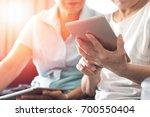 happy elderly twin senior... | Shutterstock . vector #700550404