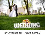 Small photo of Word wedding, big letters, man woman kiss. Beautiful young couple, wedding romantic date. Sincere devotion feelings of love charm tenderness. social problem family, fidelity in marriage, conjugal duty