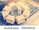 Small photo of International freight or shipping service for online shopping or ecommerce concept : Paper boxes or carton put in circle around a clear crystal globe with world map on a computer notebook keyboard.