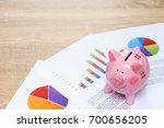 Pink piggy bank with graph on wooden desk - growing interest rate concept