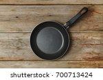 empty frying pan on a wooden...   Shutterstock . vector #700713424