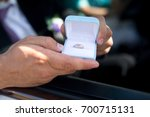 Small photo of Man hand holds small blue box with golden ring. Beautiful young couple, wedding romantic. Sincere devotion feelings of love charm tenderness. social problem family, fidelity in marriage, conjugal duty