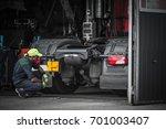 Truck Service Technician Job. Caucasian Truck Mechanic Checking on Semi Truck Tractor. - stock photo