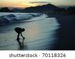 Silhouette of a boy playing at the beach at sunset - stock photo