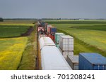 Two Trains Passing Through Vibrant Fields in Canadian Prairie - stock photo