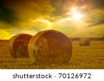 End of day over field with hay bale - stock photo